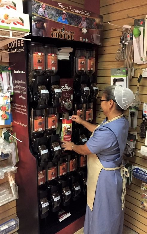 Esther re-stocks coffee on shelves at the Kauffman Family Marketplace.